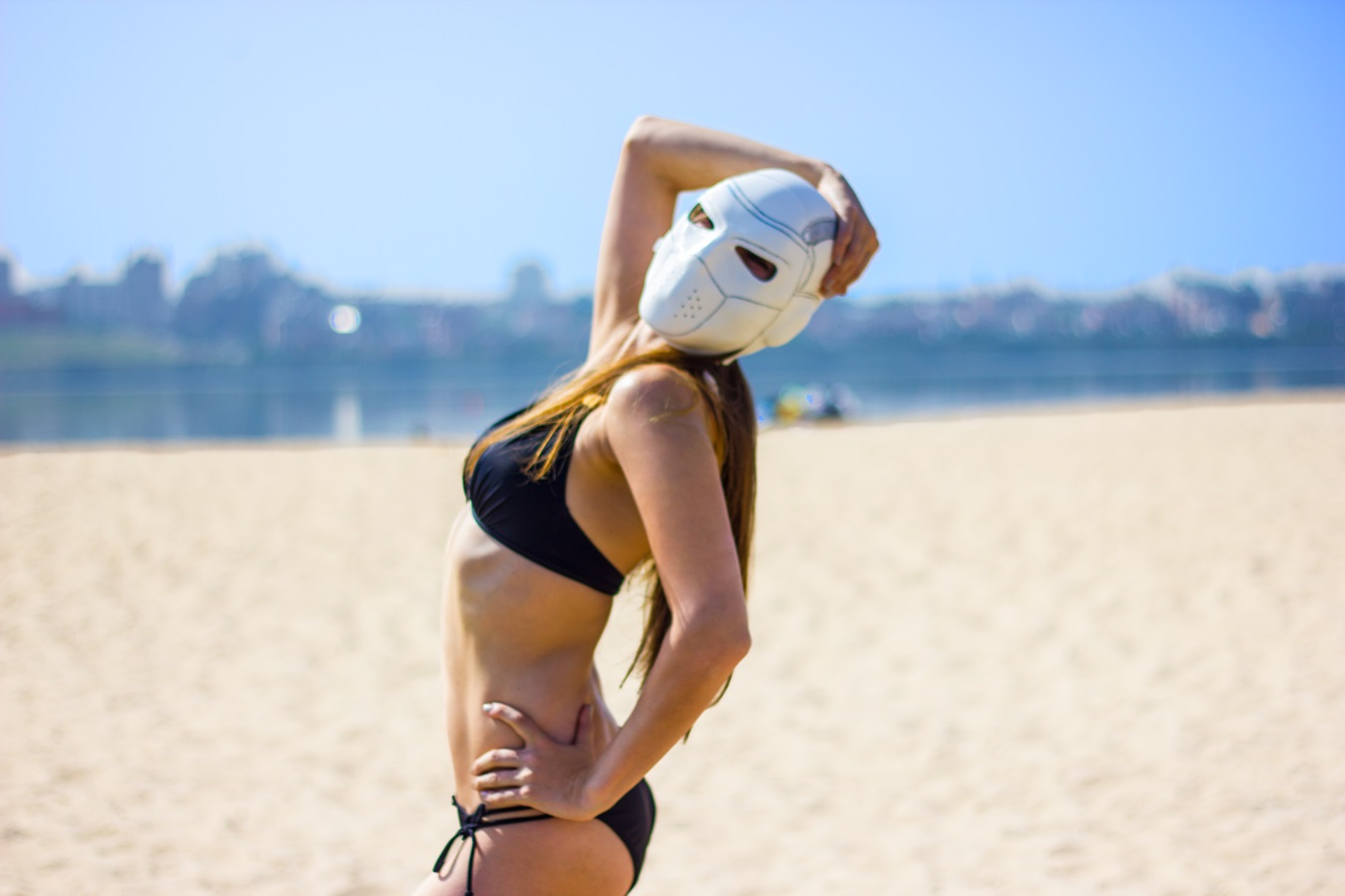 Girl in bikini posing with a deadshot mask at the beach