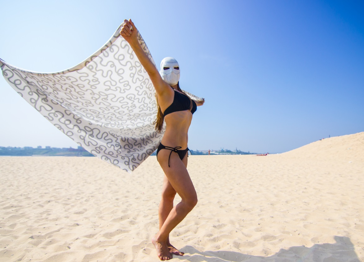Girl in bikini wearing the deadshot mask at the beach